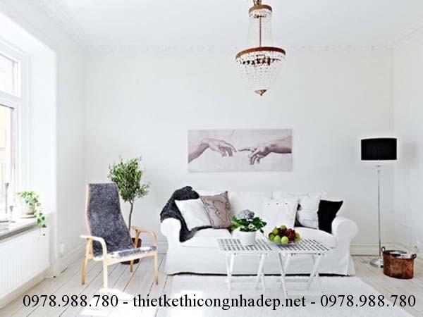 Thiết kế nội thất ngoài phòng khách với bộ sofa màu trắng nằm gọn trong một góc phòng